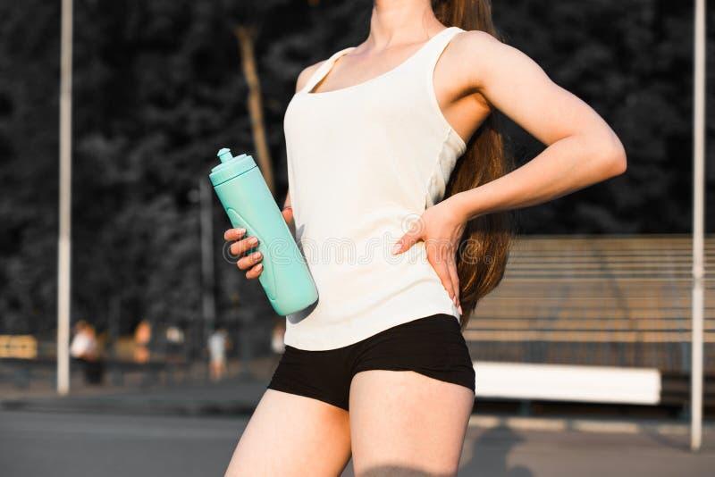 Бегун молодой женщины нагревая перед бегом на городе остатки девушки после игры спорт стоковая фотография