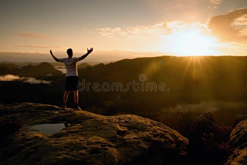 Бегун на пике Человек в его триумфе жеста цели с руками в воздухе Шальной человек в черных брюках и белой футболке хлопка, стоковое изображение rf