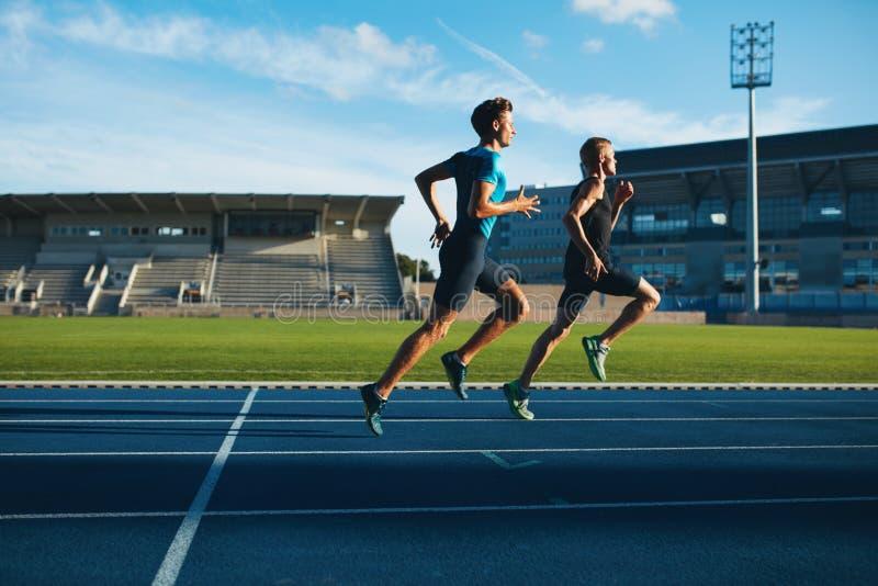Бегун практикуя в стадионе атлетики стоковое фото rf