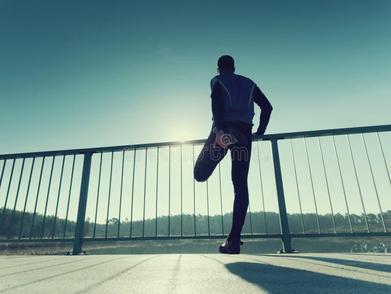 Бегун утра в высокорослых черных гетры делает тело протягивая на пути моста Внешний работать стоковое изображение rf