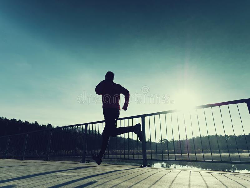 Бегун утра в высокорослых черных гетры работая на мосте Внешний работать на мосте стоковая фотография