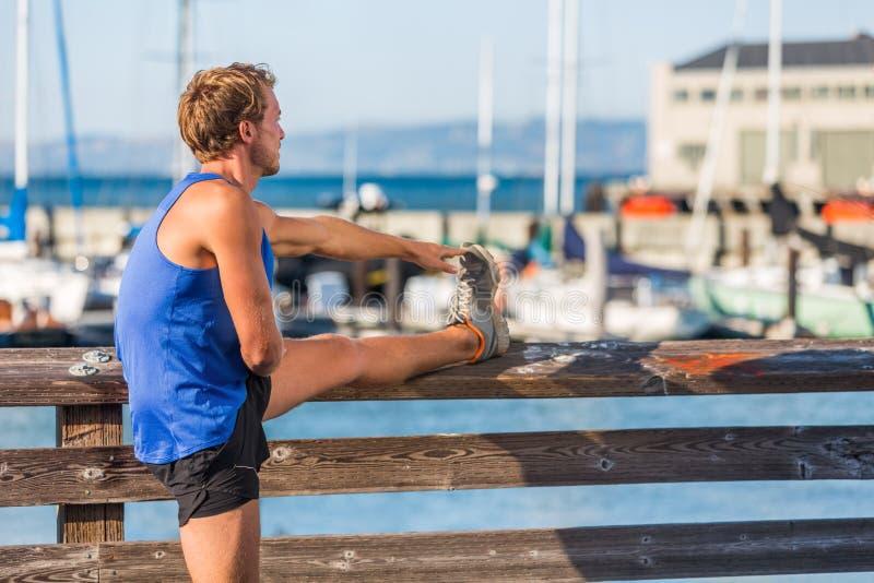 Бегун человека фитнеса протягивая мышцы ноги перед идущей тренировкой в гавани San Francisco Bay - образом жизни города Мужчина с стоковое фото rf