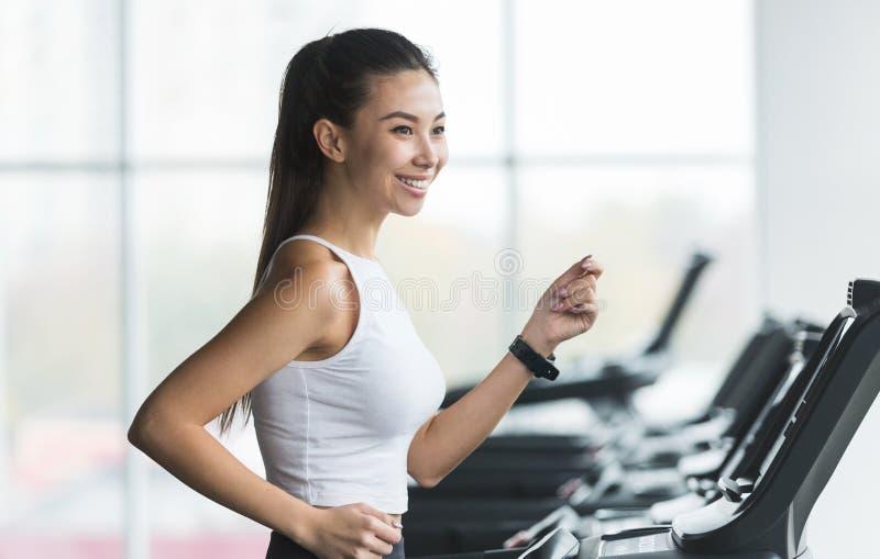 Бег на третбане Азиатская женщина делая cardio тренировку стоковая фотография rf
