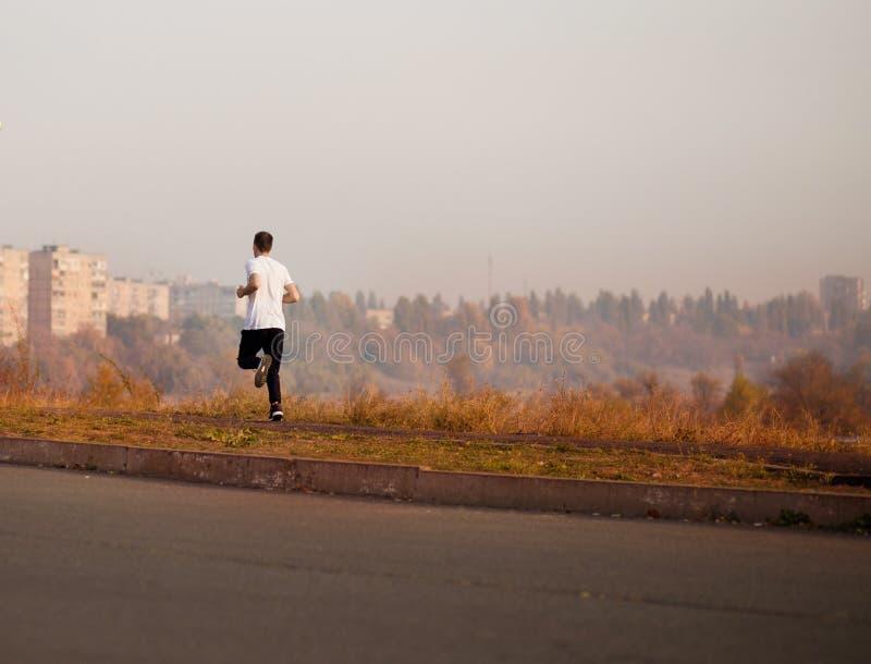 Бег человека на утре осени o стоковые фотографии rf