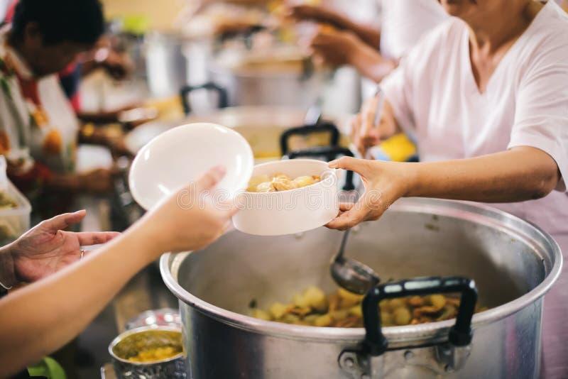 Бедные нуждаются в бесплатном питании: Пожертвования на благотворительные продукты нуждающимся нищим стоковое фото