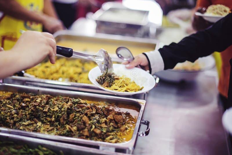Бедные нуждаются в бесплатном питании: Пожертвования на благотворительные продукты нуждающимся нищим стоковые изображения