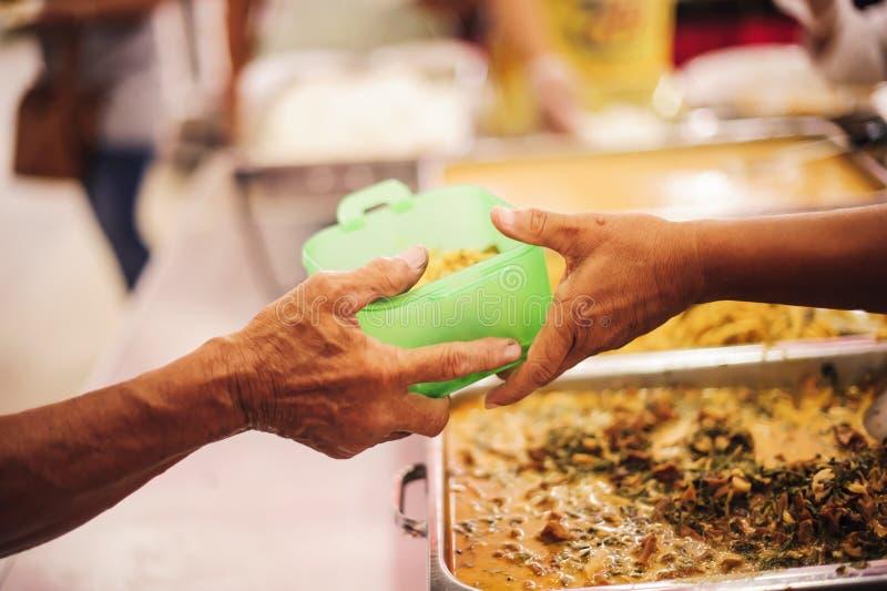 Бедные нуждаются в бесплатном питании: Пожертвования на благотворительные продукты нуждающимся нищим стоковое изображение rf