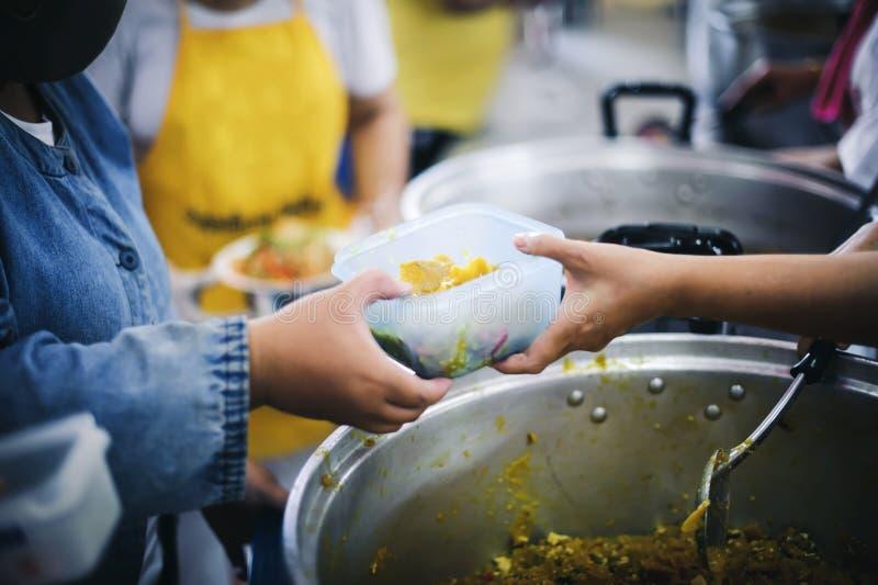 Бедные нуждаются в бесплатном питании: Пожертвования на благотворительные продукты нуждающимся нищим стоковое фото rf