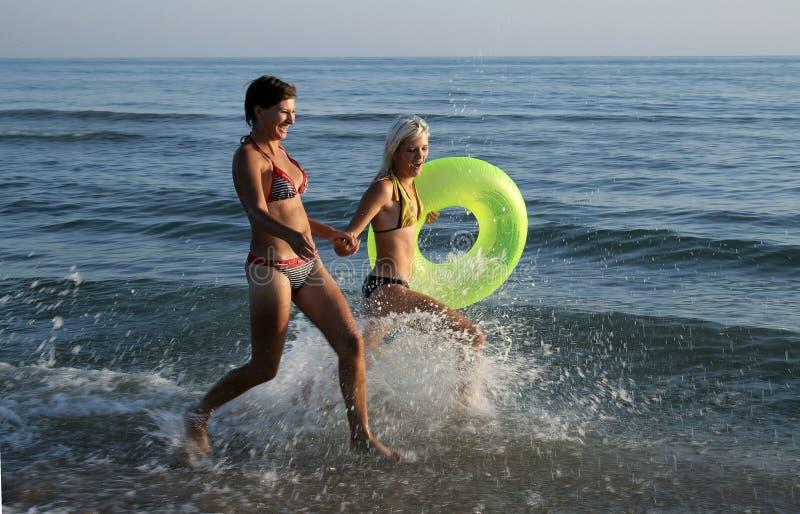 бежать девушок пляжа стоковое фото rf