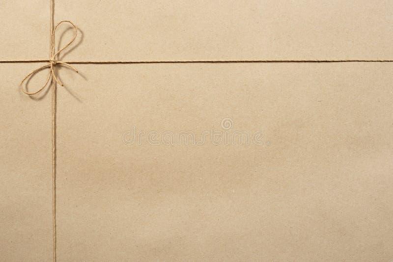 Бежевая бумага упаковки, завертывает в бумагу связанный с веревочкой стоковое фото rf