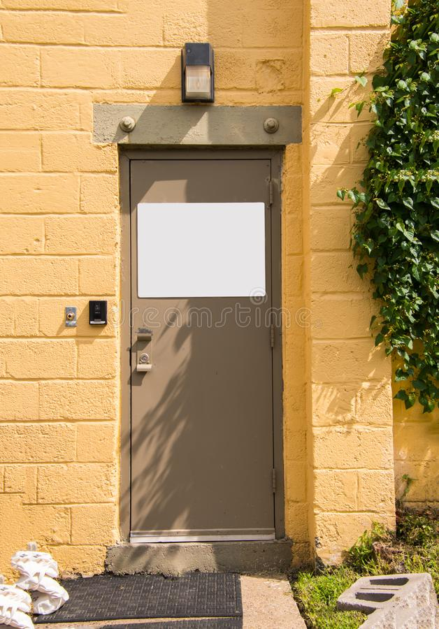 Бежевая дверь металла в желтой стене шлакоблока с белым пустым знаком стоковые фото