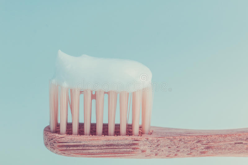Бежевая зубоврачебная щетка с белой зубной пастой на голубой предпосылке изолировано конец вверх стоковая фотография