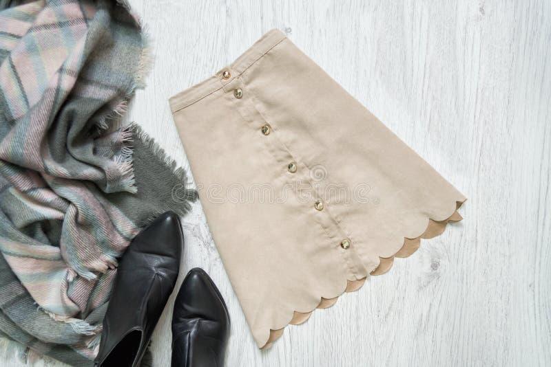 Бежевая юбка замши, черные ботинки и шарф модная концепция стоковая фотография