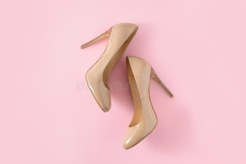Бежевые ботинки высокой пятки женщин на розовой предпосылке Взгляд блога моды Взгляд сверху, плоское положение стоковое изображение rf