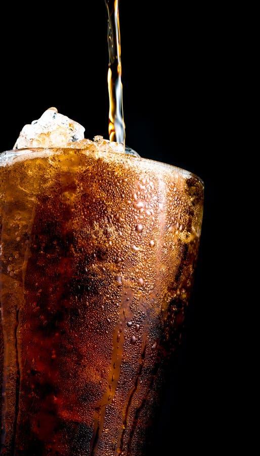 Безалкогольный напиток лить к стеклу при задавленные кубы льда изолированные на d стоковые изображения