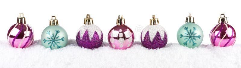 Безделушки фиолетовых, розовых & бирюзы рождества в изолированном снеге стоковое изображение rf