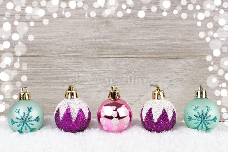 Безделушки фиолетовых, розовых и бирюзы рождества в снеге против древесины стоковое фото