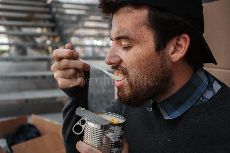 Бездомные как и бедные Гай ест мозоль от чонсервной банкы Он держит его глаза закрытый Он представляет вкусную и очень вкусную ед стоковые изображения rf