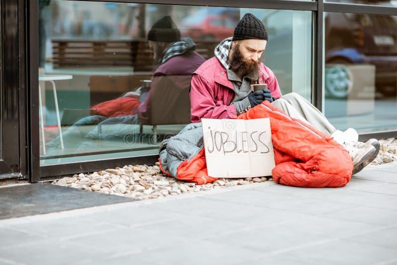 Бездомные умоляя деньги около делового центра стоковые изображения