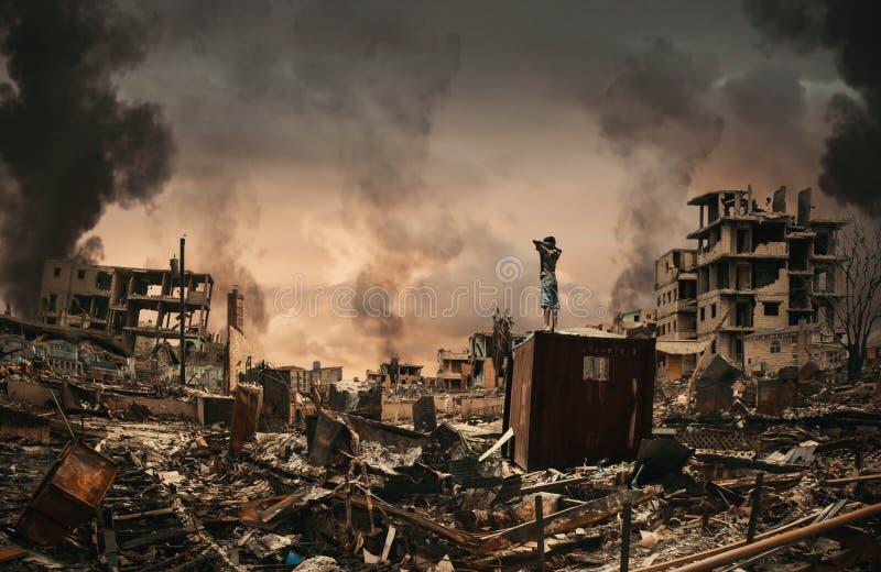 Бездомный мальчик наблюдая разрушенные дома стоковая фотография rf