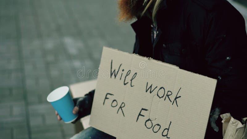 Бездомный молодой человек умоляет для денег тряся чашку для того чтобы оплатить людей внимания идя около попрошайки на тротуаре г стоковое фото rf