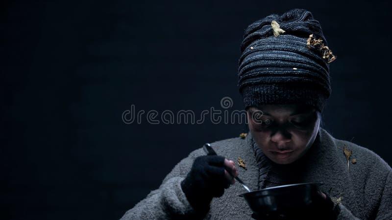 Бездомный человек жадно есть orts, голодая от голода, жизнь на улицах города стоковые фото