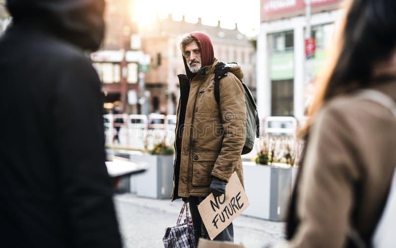 Бездомный человек попрошайки идя outdoors в город, держащ знак сумки и картона стоковые фото