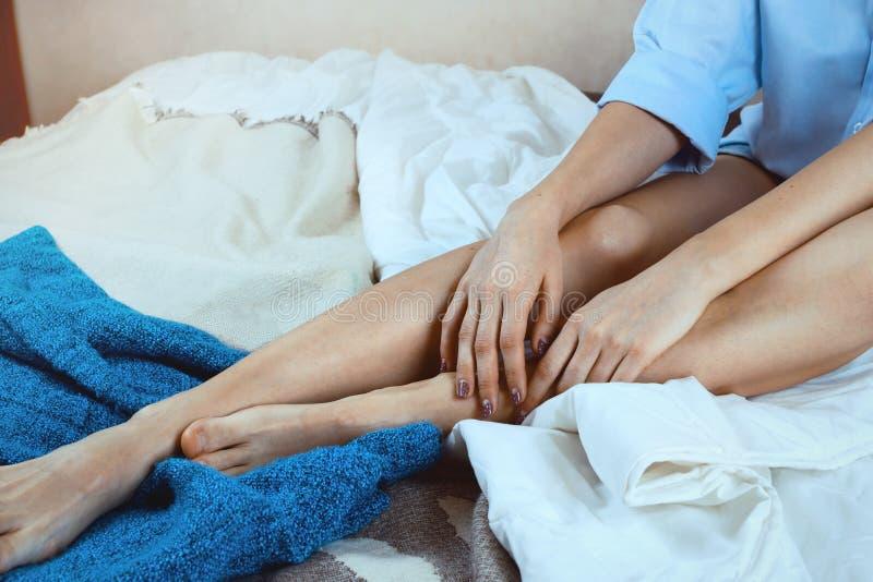 Безликая съемка рук и ног ` s женщины на кровати стоковое фото rf