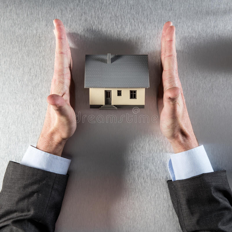 Безопасная домашняя концепция с прямым бизнесменом вручает защищая новый дом стоковая фотография
