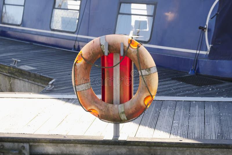 Безопасность воды кольца томбуя жизни оранжевая на Марине зачаливания шлюпки стоковое фото