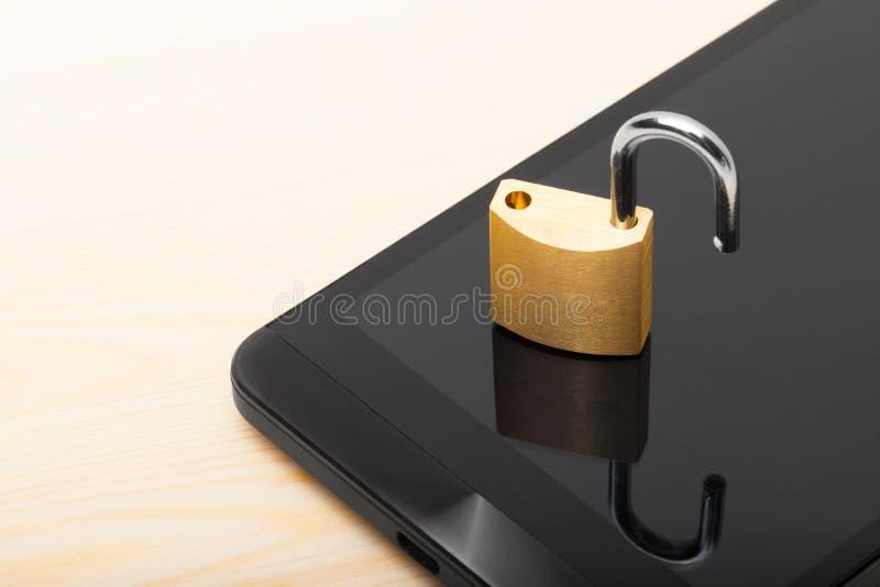 Безопасность мобильного телефона и и концепция защиты данных - малый открытый замок над smartphone стоковое изображение
