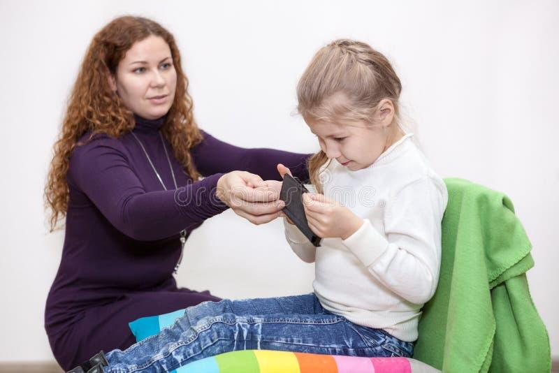 Безопасность на интернете, девушка ребенка увидела запрещенное содержание, маму принимает отсутствующий smartphone стоковое изображение rf