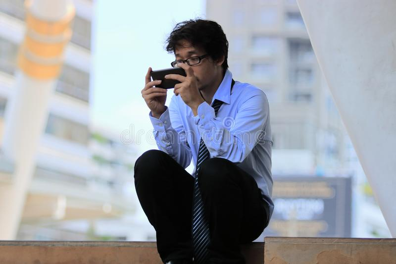 Безработный молодой азиатский бизнесмен используя передвижной умный телефон находит работа Подавленная концепция дела безработицы стоковая фотография
