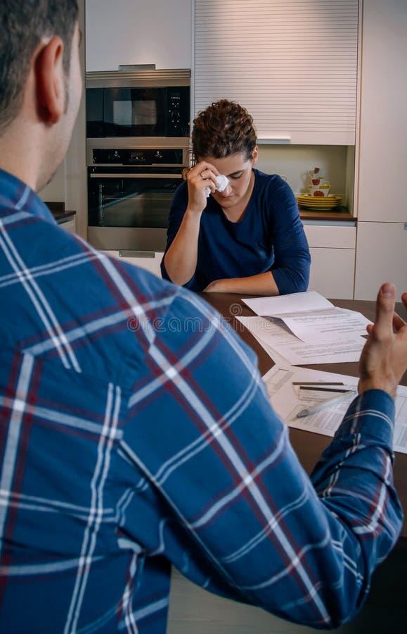 Безработный муж проверяет счета, жена плачет по долгам стоковые изображения rf