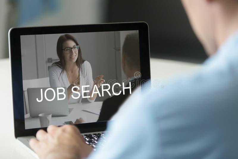 Безработный человек используя компьтер-книжку ища работу онлайн, применяющся для стоковая фотография