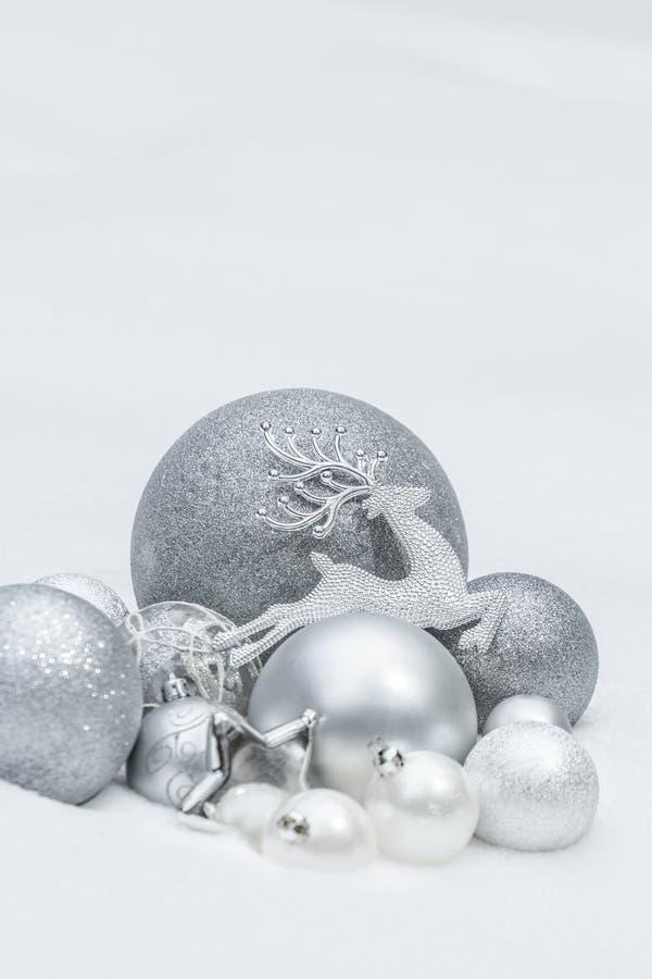Безделушки и звезда рождества праздника серебряные декоративные с северным оленем Санта Клауса на естественной предпосылке снега стоковая фотография rf
