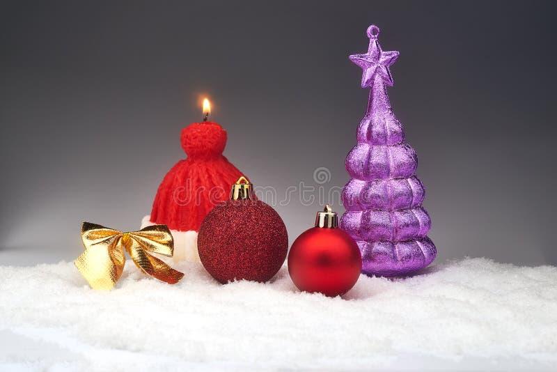 Безделушки и свеча рождества на снеге стоковое изображение rf