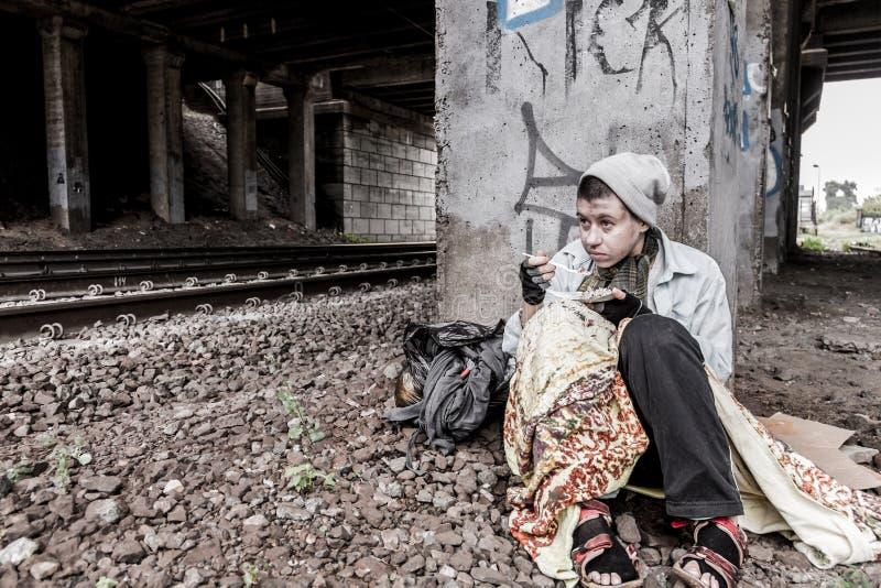 Бездомная женщина имея еду стоковое изображение rf