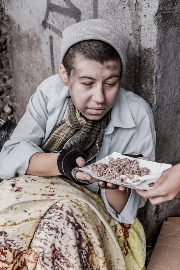 Бездомная женщина получая еду стоковые изображения rf