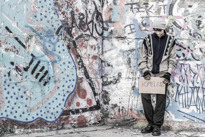Бездомный молодой человек стоит около стены стоковое изображение rf