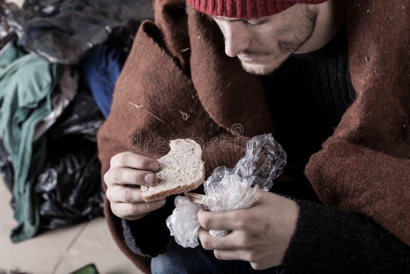 Бездомный человек есть сандвич стоковая фотография
