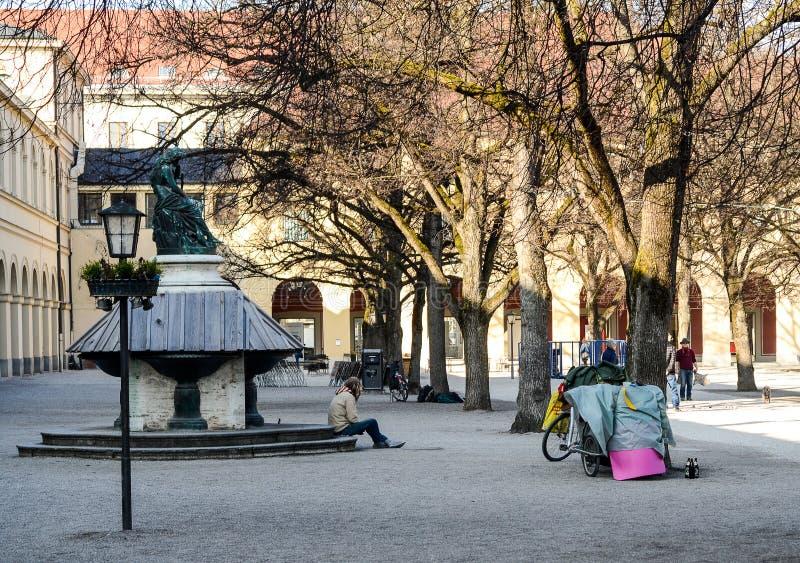 Бездомный человек сидит, который взошли на борт фонтаном стоковые изображения