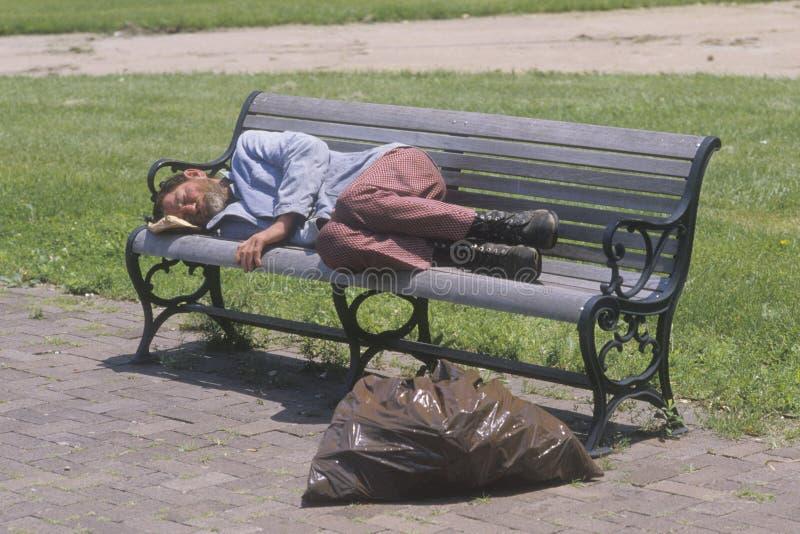 Бездомный человек спать на скамейке в парке, Лос-Анджелес, Калифорния стоковые изображения rf