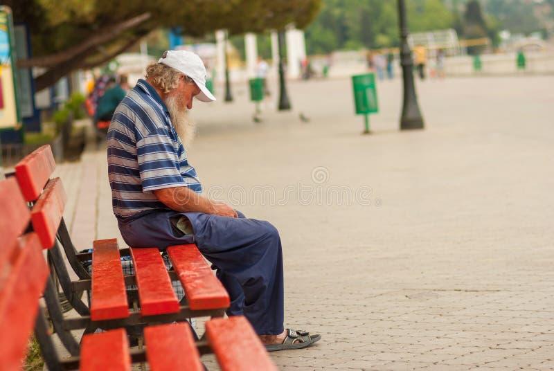 Бездомный человек спать пока сидящ на черном стенде берега моря стоковая фотография