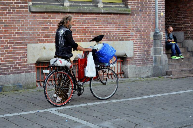Бездомный человек с его велосипедом и его вороной стоковое изображение rf