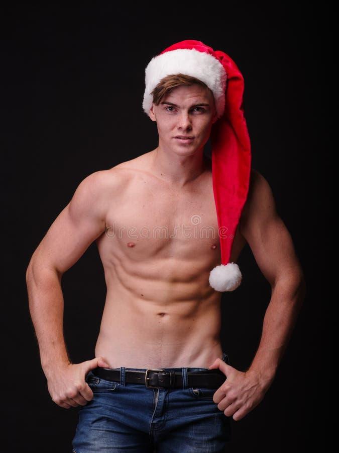 Без рубашки культурист в крышке santa на черной предпосылке Сексуальный мужской santa Концепция рождественской вечеринки стоковые фотографии rf