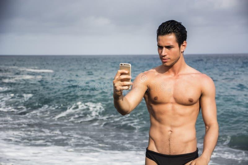 Без рубашки молодой человек принимая фото Selfie на пляж стоковое фото