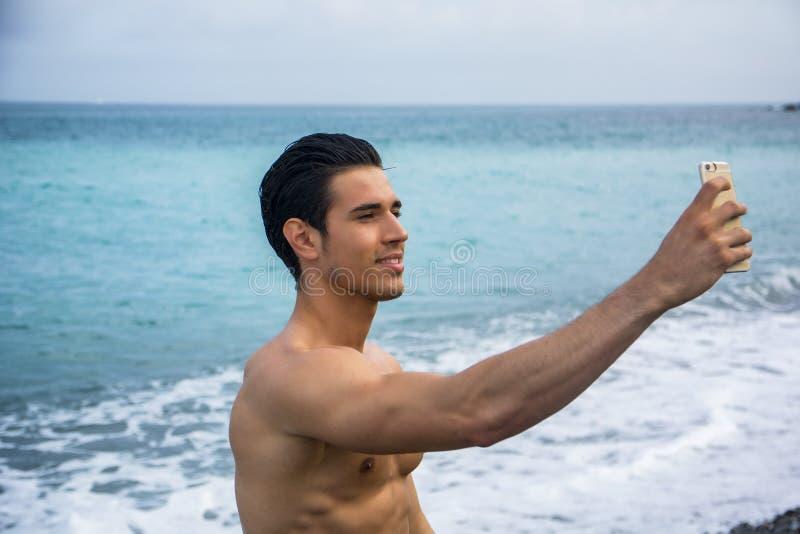 Без рубашки молодой человек принимая фото Selfie на пляж стоковая фотография rf