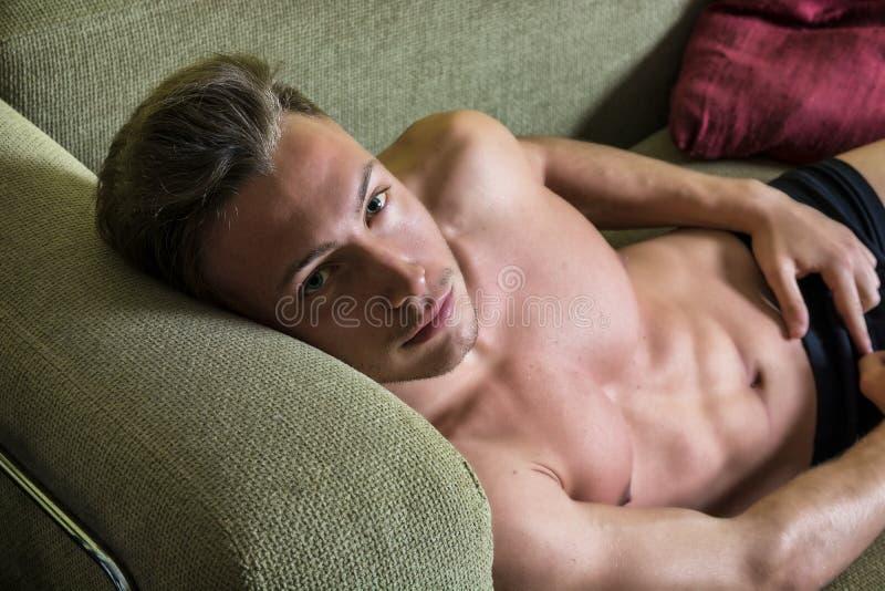 Без рубашки мышечный молодой человек дома на кресле стоковое фото rf