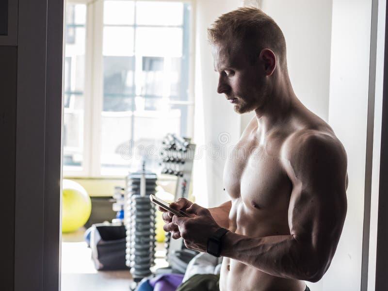 Без рубашки мышечный человек используя сотовый телефон в спортзале стоковые фотографии rf